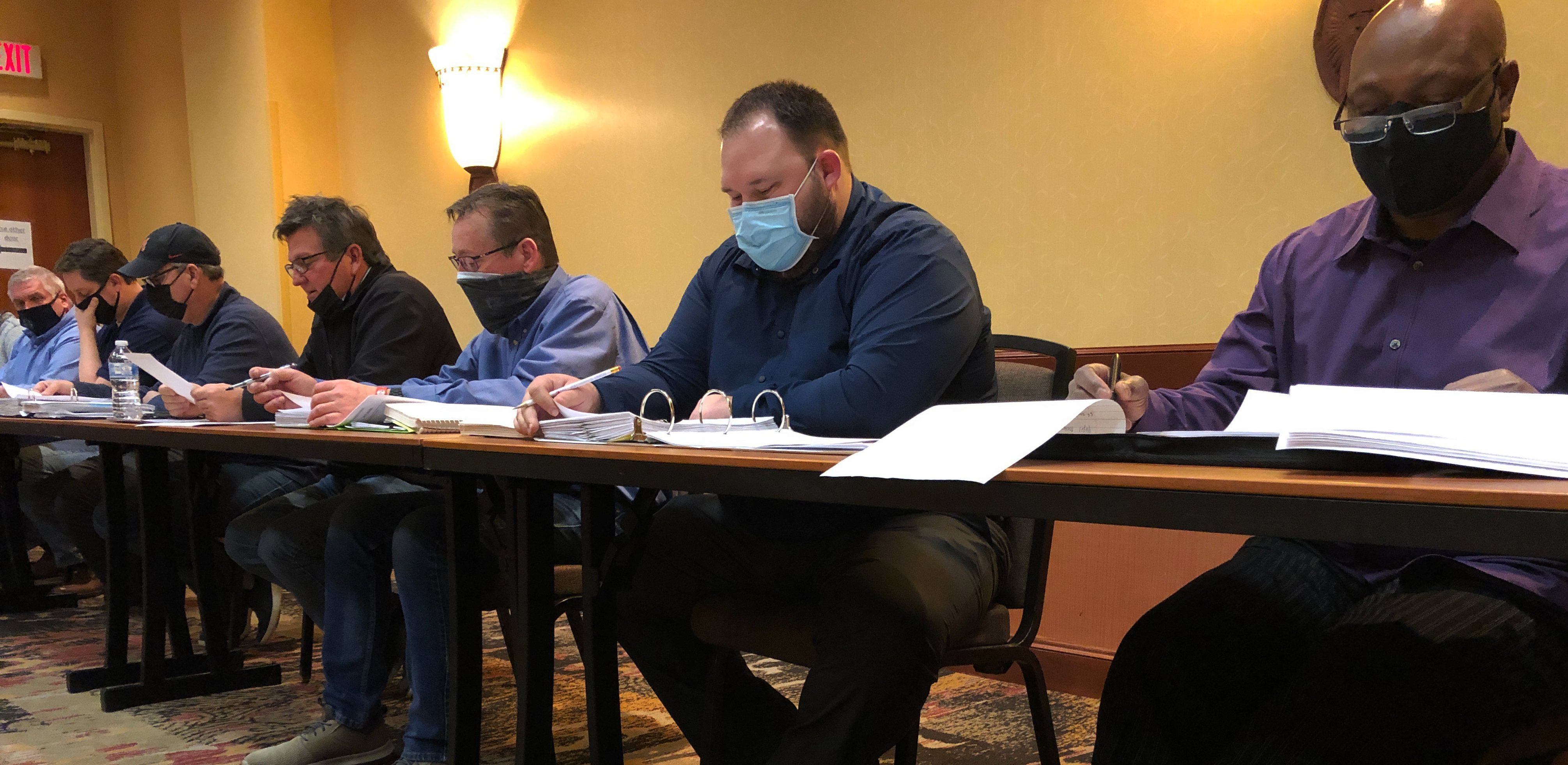 A photo of the negotiating committee at the table with masks on.