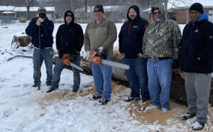 Six members standing outside in the snow with chainsaws after cutting wood.
