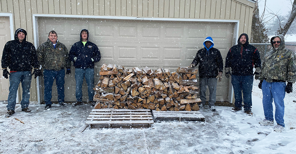 Negotiating Committee outside with a wood pile in the snow.